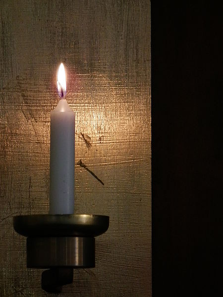 Single white lit candle